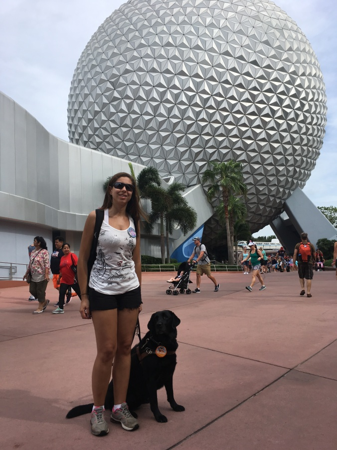 Mellina está em pé com sua cão-guia sentada a direita dafoto, ao fundo aparece o Globo do Epcot Center, o globo é bemgrande