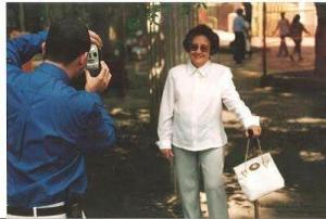 Descrição da foto - Foto antiga, Beto de costas de camisa social azul e com as duas mãos segura uma câmera fotografando a sua avó de camisa branca social, usando óculos escuros e calça cinza. A senhora está de bengala e uma bolsa branca na mão esquerda. De fundo o local aparenta ser uma praça ou um parque.