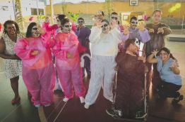 Descrição da foto: 14 pessoas em uma quadra esportiva enfeitada, intercalando entre pessoas com deficiência intelectual e professores, estão fantasiados estilo roupa macacão feito de tecido TNT (cada um de uma cor representando um animal: gato, urso, galinha,porco...) Algumas pessoas estão com uma pintura de gato no rosto, outros usam máscaras.