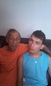 Descrição da foto - Sr. Nyceu e Daniel estão sentados no sofá de tonalidade escura; Sr Nyceu está com o braço esquerdo sobre o pescoço do Daniel (meio abraço) Sr. Nyceu está com camiseta laranja e Daniel com camiseta regata retrô azul claro.